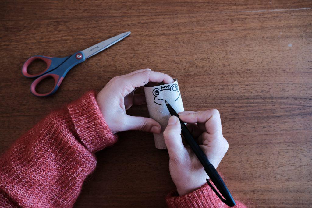 Puppe wird mit Stift auf Papierrolle gemalt
